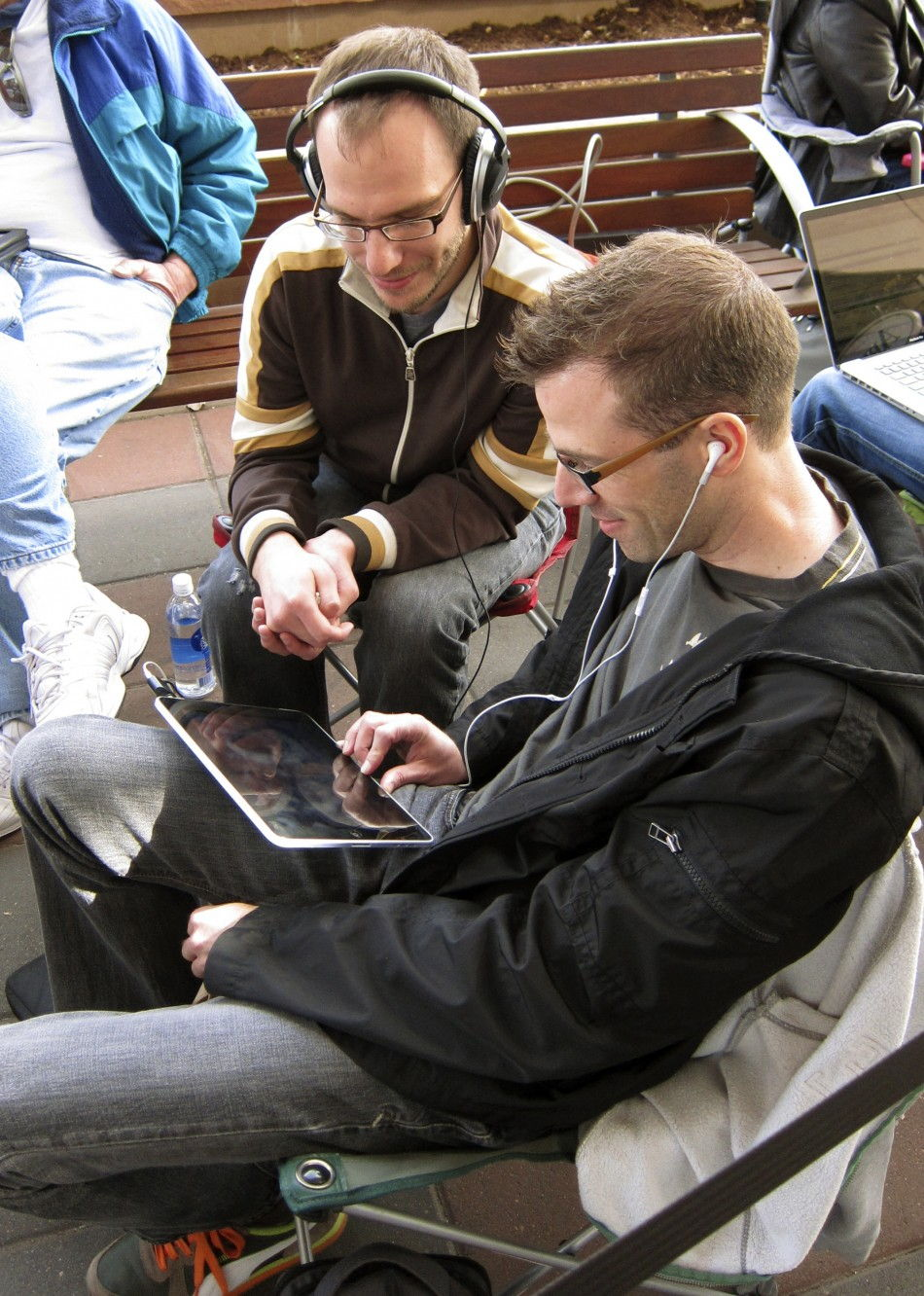73602-two-men-watch-a-movie-on-an-ipad-as-they-wait-outside-the-apple-store-